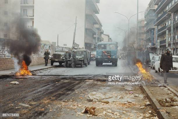 View of policemen patrolling a street with burning barricades in the Sbarre district of Reggio Calabria following a period of rioting by residents...