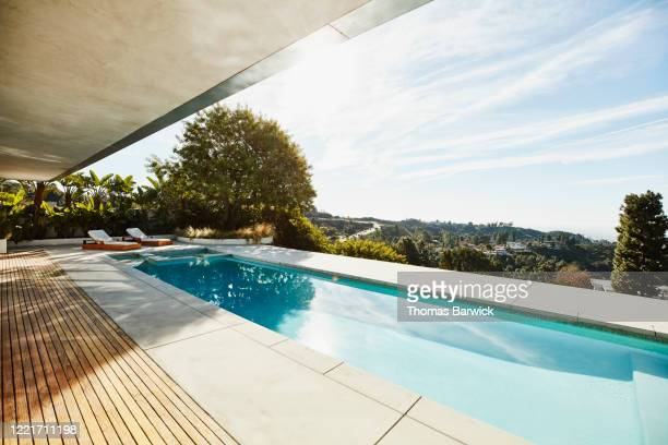 view of pool in backyard of modern home - sun lounger stock pictures, royalty-free photos & images
