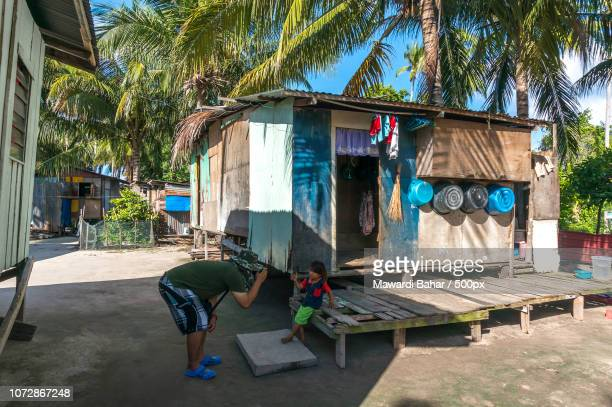 sabah, malaysia - august 16, 2016 : a view of poor wooden house and people at mabul island, sabah ma - mabul island stock photos and pictures