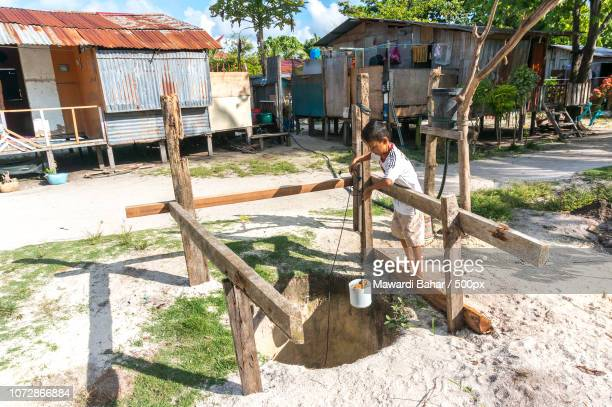 mabul island, malaysia - august 16, 2016 : view of poor wooden house and villagers at mabul island, - mabul island stock photos and pictures