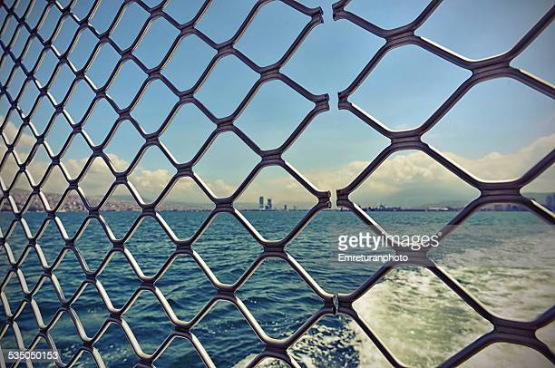 view of port and cityscape behind fence - emreturanphoto stock pictures, royalty-free photos & images