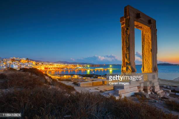view of portara and remains of temple of apollo at sunset. - naxos stockfoto's en -beelden