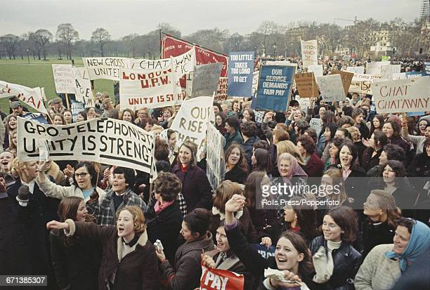 View of post office employees including GPO telephone operators holding banners and placards as they march through Hyde Park in London for a rally...