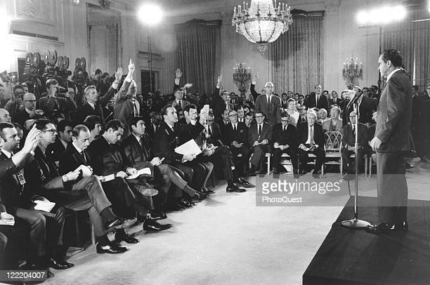 View of President Richard M Nixon standing at a podium addressing questions from reporters during his first press conference in the East Room of the...