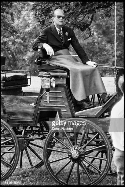 View of Prince Philip, Duke of Edinburgh , in dark glasses and a suit and tie, as he sits, with a blanket across his lap, in the driver's seat of a...
