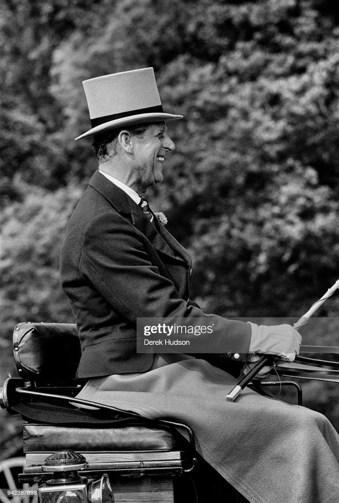 View of Prince Philip, Duke of Edinburgh, in formal attire including a top hat and gloves, as he laughs from the driver's seat of a carriage during a driving event, Home Park, Windsor, England, July 1975.