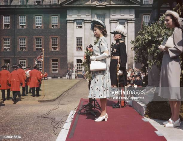 View of Princess Elizabeth standing on a dias as she inspects a parade of Chelsea Pensioners at the Royal Hospital Chelsea in London on 29th May 1947.