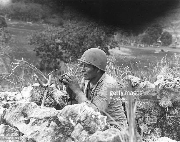 View of Private First Class Carl Gorman an Indian Marine as he mans an observation post on a hill overlooking the city of Garapan while the Marines...