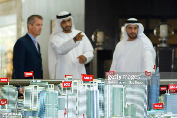 View of property model in foreground and men in traditional Middle Eastern dress meeting Western businessman, Dubai, UAE