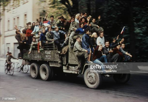 View of protesters and residents of Prague Czechoslovakia riding on a military vehicle on a city street in the capital during the Soviet and Warsaw...