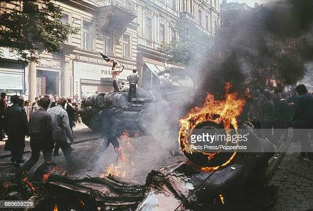 View of protesters and residents of Prague Czechoslovakia standing on and around a Russian tank as a wrecked motor vehicle burns on a city street in...
