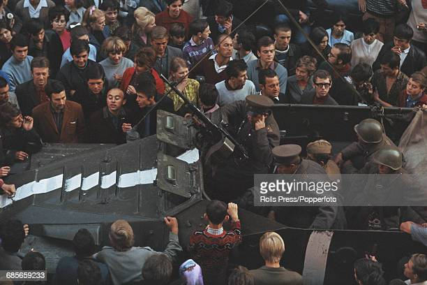 View of protesters and residents of Prague Czechoslovakia surrounding a Russian military vehicle manned by members of the Soviet Army on a city...