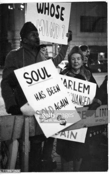 View of protestors including American artist Alice Neel as they hold signs and demonstrate outside the Metropolitan Museum of Art during the 'Harlem...