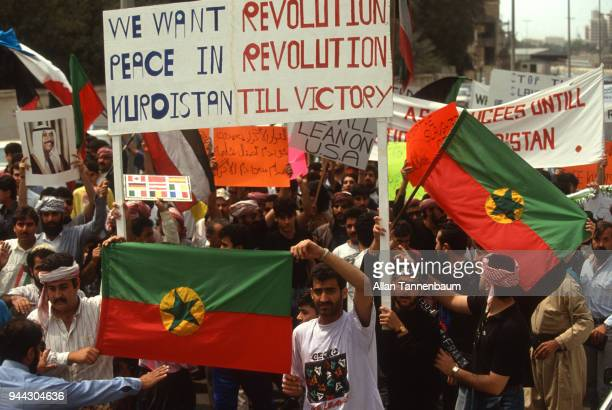 View of protestors many with signs and flags as they march during a peace demonstration during the Gulf War Iraq 1991 Among the visible signs is one...