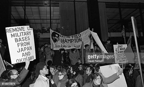 View of protestors many with signs or banners at an antiNixon demonstration outside the WaldorfAstoria hotel New York New York December 9 1969 One...