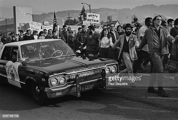Protesters holding hands march past a California Highway Patrol police car during the Vietnam Day Protest at the University of California Berkeley...
