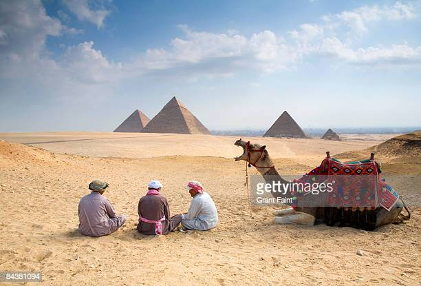 view of pyramids with camel drivers sitting with c