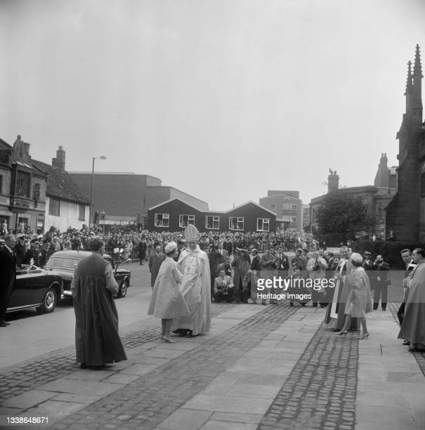 View of Queen Elizabeth II and the Bishop of Coventry standing on the pavement outside Coventry Cathedral on the day of the consecration service,...