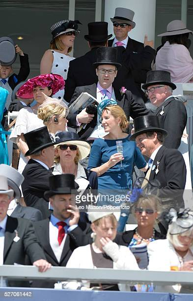 View of racegoers and spectators in formal dress watching the horse racing at the Investec Derby Day race meeting at Epsom Downs racecourse in Epsom...