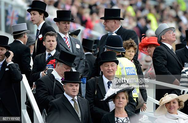 View of racegoers and spectators in top hats and bowler hats watching the action at the Investec Derby Day Race Meeting at Epsom Downs racecourse in...