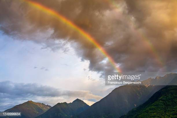 view of rainbow against colorful storm clouds above mountains at sunset. - italia ストックフォトと画像