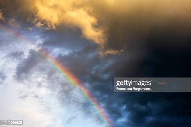 view of rainbow against colorful storm clouds. - italia ストックフォトと画像