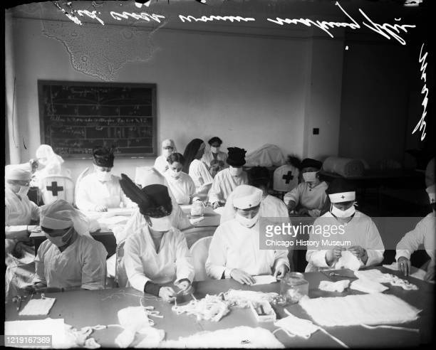 View of Red Cross staff members, seated at long tables, as they make influenza masks during the ongoing pandemic, Chicago, Illinois, 1918.