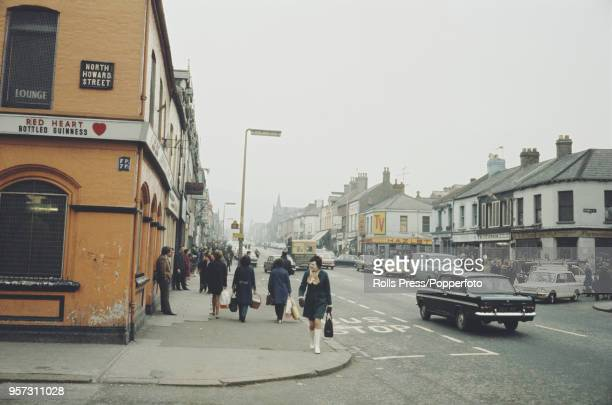 View of residents visiting shops and businesses in the predominantly republican Falls Road area of west Belfast, Northern Ireland during The Troubles...