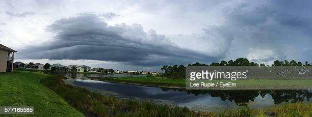 View Of River Amidst Grassy Field Against Cloudy Sky
