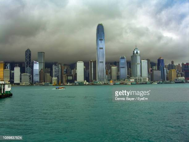 view of river by cityscape against sky - storm dennis stock pictures, royalty-free photos & images