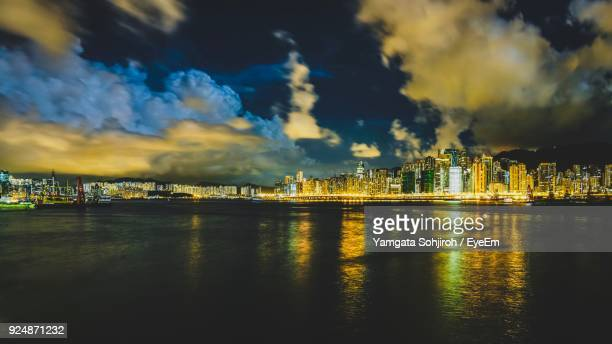 View Of River By Illuminated Buildings Against Sky At Night