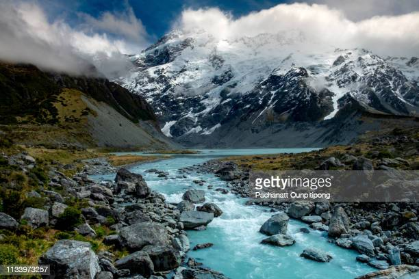 view of river in front of snowcapped mountain with some clouds on some part of top mountain at hooker valley track in aoraki/mount cook national park, new zealand - purity stock pictures, royalty-free photos & images