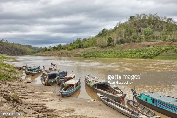 view of river sangu (bandarban) flowing through chittagong hill tracts with several canoes beached on the riverbank in rainy weather, bangladesh - bangladesh nature stock pictures, royalty-free photos & images