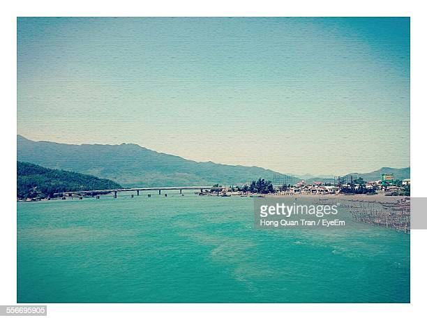 view of river with bridge and mountains - hong quan stock pictures, royalty-free photos & images