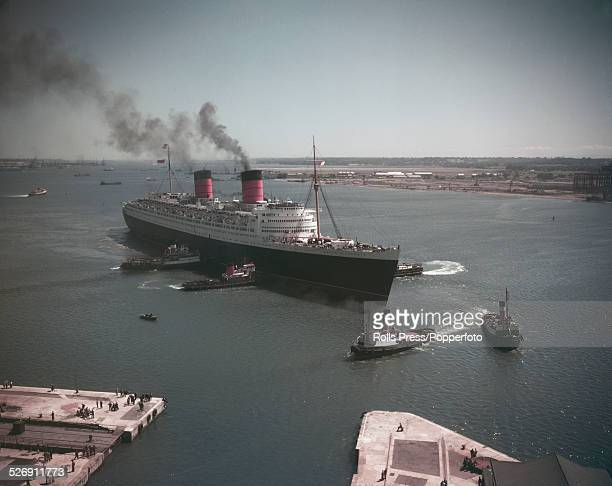 View of RMS Queen Elizabeth liner being guided by tug boats in Southampton Water after departing from the port of Southampton bound for New York...