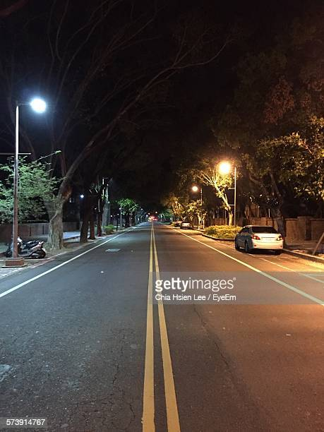 view of road against sky at night - double yellow line stock photos and pictures