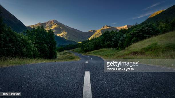 View Of Road Amidst Mountains Against Blue Sky
