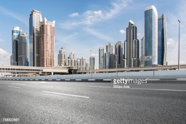 view of road and modern glass skyscrapers in financial district, dubai, united arab emirates - image stock pictures, royalty-free photos & images