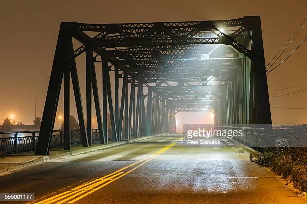 view of road and silhouetted iron bridge at night, tacoma, washington, usa - 工場地帯 ストックフォトと画像