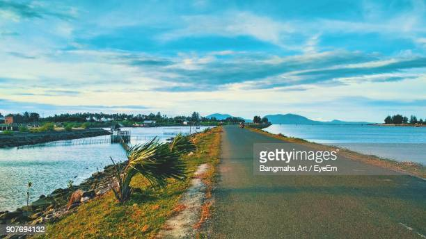 view of road by river against cloudy sky - aceh stock pictures, royalty-free photos & images