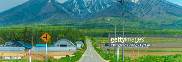 view of road passing through landscape - biei town stock pictures, royalty-free photos & images