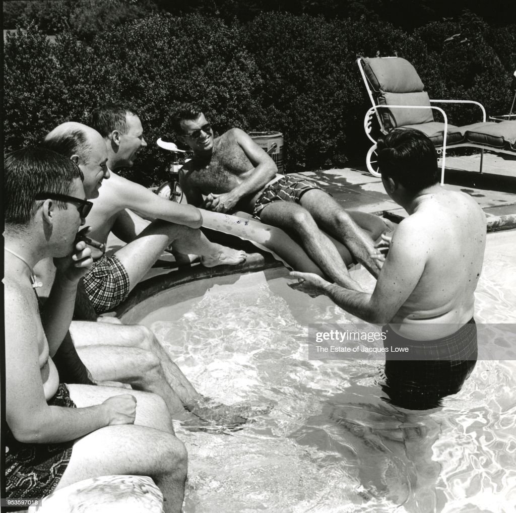 View of (future US Attorney General) Robert F Kennedy (1925 - 1968) (second right, in sunglasses) as he laughs with unidentified others around the edge of a pool, late 1950s or 1960s.