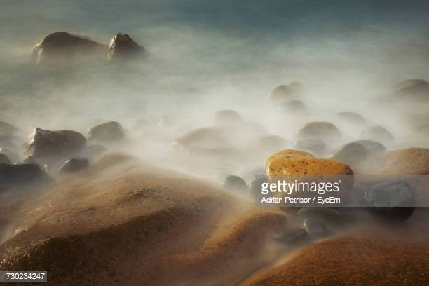 View Of Rock Formation In Water Against Sky