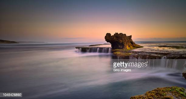 view of rock formations in ocean at sunset, australia - image stock pictures, royalty-free photos & images