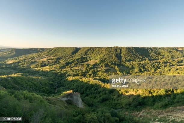 view of rolling landscape against clear blue sky, italy - image foto e immagini stock