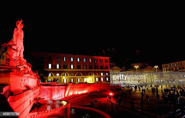 A view of Rome's Piazza del Popolo illuminated in red on November 25 2014 in support of the UNbacked International Day for the elimination of...