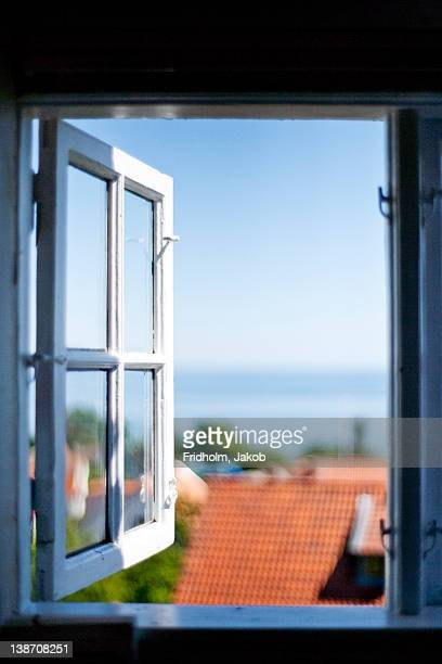 View of rooftop of house through open window