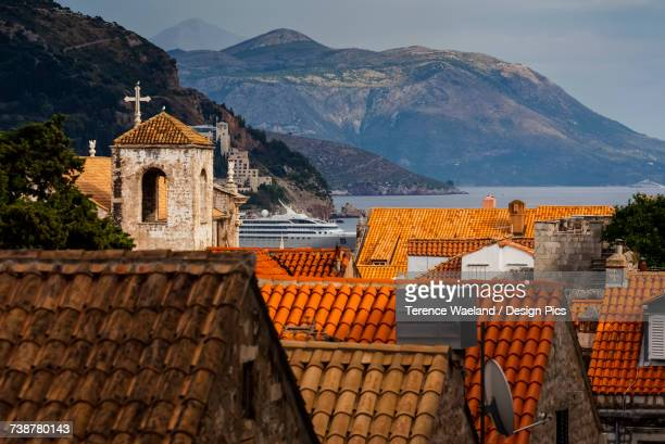 view of rooftops, a tower with a cross and the coastline - terence waeland stock pictures, royalty-free photos & images