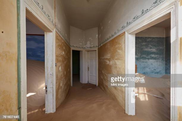 A view of rooms in a derelict building full of sand.
