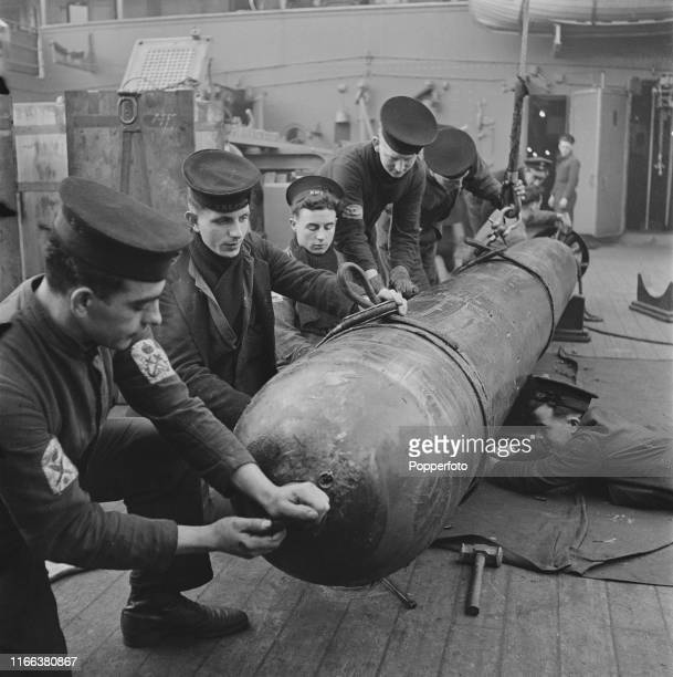 View of Royal Navy ratings making final adjustments to a torpedo on board the Royal Navy submarine depot ship HMS Forth prior to loading on to a...